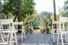 Magnificent Decoration Of A Wedding Ceremony With Original Details And Candles. Wedding Reception Zone. Round Arch