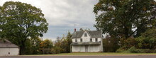 Abandoned White Farmhouse With Boarded Windows And Delapidated Porch In Summer