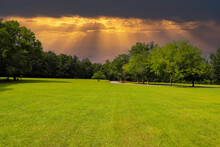 A Long Stretch Of Lush Green Grass Surrounded By Lush Green And Autumn Colored Trees In The Park With Powerful Clouds Near A Paved Road At McIntosh Reserve Park In Whitesburg Georgia