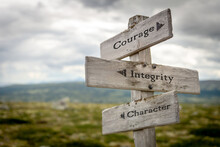 Courage Integrity Character Text On Wooden Signpost Outdoors In Landscape Scenery.