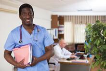 Portrait Of Friendly Male Doctor Wearing Uniform With Folder