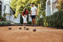 Cheerful Young Couple Playing Boules Together