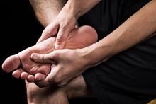 足の裏を押さえる男性の手