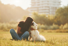 Embracing The Pet. Woman With Her Dog Is Having Fun On The Field At Sunny Daytime