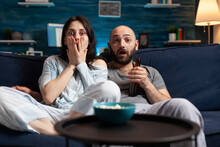 Confused Shocked Couple Watching TV Movie At Night And Eating Popcorn, Drinking Beer Having Fear Facial Expression. Focused Astonished People Sitting On Confortable Couch Chilling Together
