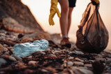 Close up of blue plastic bottle lying on the beach. Close up of volunteer's hands with plastic bag picks up a bottle. The concept of Earth Day and envinmental pollution