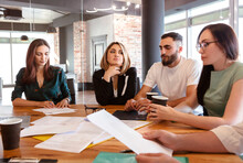 Creative Team Of Four Diverse Pensive Young Business People Gathered For Weekly Meeting In Office