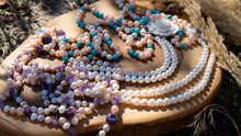 Variety Of Iridescent Natural Pearl And Amethyst Beads On A Wooden Background. Retro Composition Close Up. Natural Mineral.