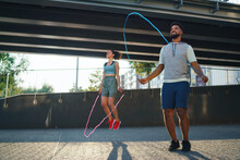 Man And Woman Couple Friends Doing Workout Exercise Outdoors In City, Skipping.