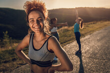 Portrait Of Young Woman Preparing For Running With Her Friends Outdoors.