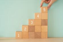 ステップアップ、レベルアップ|1から5までの数字が書かれた積み木と人の手