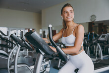 Dreamful Minded Happy Young Strong Sporty Athletic Sportswoman Woman 20s In White Sportswear Earphones Listen Music Look Aside Warm Up Training Use Exercise Bike In Gym Indoor Workout Sport Concept