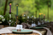 Close Up Of Rustic Place Settings And Candles For A Woodland Naming Ceremony.