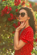 Curly Beautiful Woman With Fashionable Sunglasses In Red Dress With Polka Dots With Silver Bracelet Posing Near Roses In Nature
