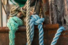 Knotted Blue Rope Laying Over The Side Of A Rusting Frame And Hull Of A Deep Sea Trawler