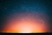 Amazing Beautiful Night Sky Glowing Stars Background Backdrop With Colorful Sky Gradient. Sunset Sunrise Light And Colourful Night Starry Sky In Blue Yellow Pink Orange Colors. Dark Ground Silhouette