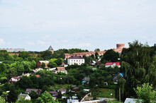 Panorama Of Smolensk. Red Brick Wall And Tower. Small Wooden Houses Near The Walls Of The Kremlin.