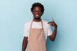 Young african american store clerk isolated on blue background person pointing by hand to a shirt copy space, proud and confident