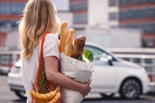 Woman With Groceries Walks To Her Car In A Supermarket Parking Lot. Customer With Reusable Bags Honor A Sustainable Lifestyle With Zero Waste And Plastic Free Shopping
