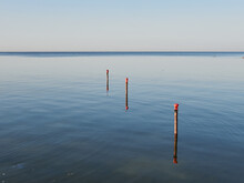 Columns With Red Markings For Mooring Catamarans And Boats.