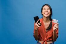 Young Asia Lady Using Phone And Credit Bank Card With Positive Expression, Smiles Broadly, Dressed In Casual Clothing And Stand Isolated On Blue Background. Happy Adorable Glad Woman Rejoices Success.
