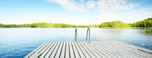 Wooden Pier Near The River Close-up. Evergreen Coniferous Forest In The Background. Clear Blue Sky, Reflections On The Water. Idyllic Summer Landscape. Eco Tourism, Recreation Theme. Finland