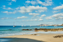 Beach With Sailboats In The Background