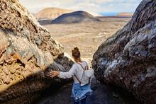 Female Traveler Touching Rocky Surface