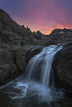 Fast Waterfall On Ridge Under Sunset Sky