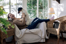 Laughing Woman In Headset With Fox Terrier In Armchair