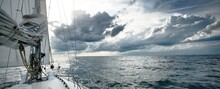 White Yacht Sailing In An Open Sea On A Summer Day. Close-up View From The Deck To The Bow And Sails. Waves And Water Splashes. Dramatic Sky, Storm Clouds. Netherlands