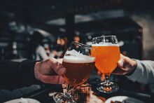 Two Glass Of Beer In Hand. Beer Glasses Clinking In Bar Or Pub