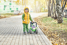 Sweet Little Boy In Bright Yellow Vest Stands And Smiles Near Ride-on Toy Walking On Paved Road In Sunny Autumn Park