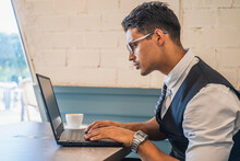 Hispanic Businessman Concentrating On Reading On His Laptop