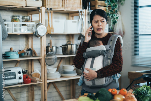 Fotografia unhappy chinese asian mom is frowning while talking on the phone with her newborn baby in the carrier at the home kitchen