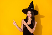 Photo Of Optimistic Millennial Brunette Hairdo Lady Point Empty Space Wear Black Dress Witch Cap Isolated On Yellow Color Background
