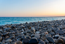 Stony Pebble Beach In Sunset Mood And Blue Sea Water, Concept Of Vacation, Wanderlust And Freedom