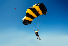 Parachute In The Sky. Skydiver Is Flying A Parachute In The Blue Sky.