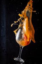 Glass With Splashing Orange Cocktail