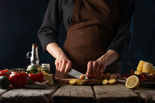 The Chef Is Cutting Potatoes On A Cutting Board. He Prepares Boiled Corn With Crayfish And Vegetables. Traditional American Dish. Close-up. Step By Step Recipe.