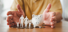 Businessman Take A Position To Protect On The Piggybank And Paper Family In Hand, Donation, Saving, Charity, Family Finance Plan Concept, Fundraising, Superannuation, Financial Crisis Concept