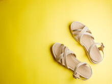 Close Up Of Beige Leather Summer Comfortable Women's Sandals On Brigth Yellow Paper Background. Top View, Flat Lay, Horizontal, Copy Space