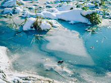 Snowy Shore Of A Frozen River. Winter Landscape With Grass Covered With Snow.