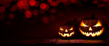 Three Scary Halloween Lanterns With Evil Eyes And Faces On A Rustic Wood Table With A Spooky Dark Red Background With Faint Red Bokeh.