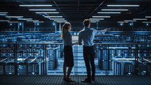 Data Center Male It Specialist And Female System Administrator Talk, Use Laptop. Server Farm Cloud Computing Facility With Two Information Technology Professionals Working On Cyber Secury.