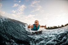 Cheerful Man Wakesurfer Lying On Board Rides Down Wave And Show Hands Gestures