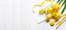Spring Banner With Yellow Tulips And Macarons On A White Wooden Background. Flat Lay Style