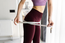Dieting Concept. Woman With Measuring Tape In The Room At Home
