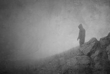 A Dream Like Concept Of A Hooded Spooky Figure Looking Out Over A Foggy Hill. With A Grunge, Vintage, Textured Edit