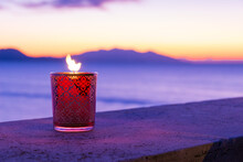 Candle Glass At Sunset In Italy, Sea And Elba Island, In The Background